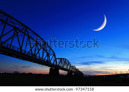 aged and old railroad bridge silhouette in the night with moon - stock photo