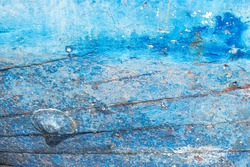 Aged and textured blue paint on a fishing boat hull