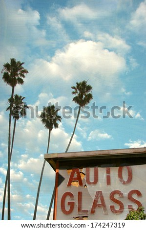 aged and worn photo of auto glass sign with palm trees