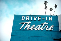 aged and worn vintage neon drive-in theater sign