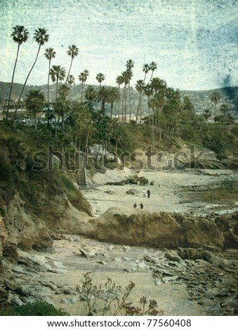 aged and worn vintage photo of beach with palm trees and rocks