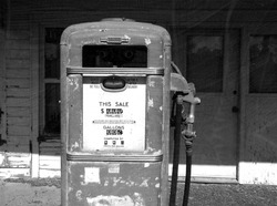 aged and worn vintage photo of black and white retro gas pump