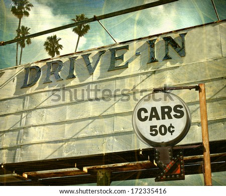 aged and worn vintage photo of drive in movies sign with palm trees
