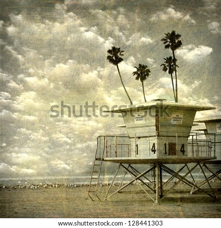 aged and worn vintage photo of lifeguard towers on beach with palm trees