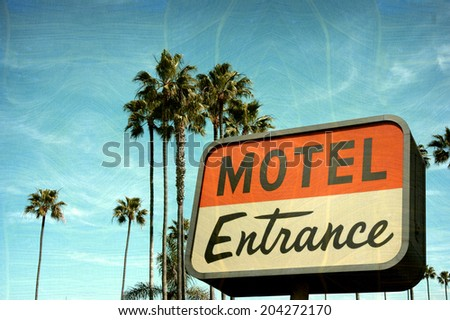 aged and worn vintage photo of motel entrance sign with palm trees
