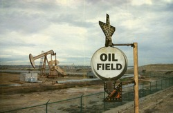 aged and worn vintage photo of oil field sign with derrick in background