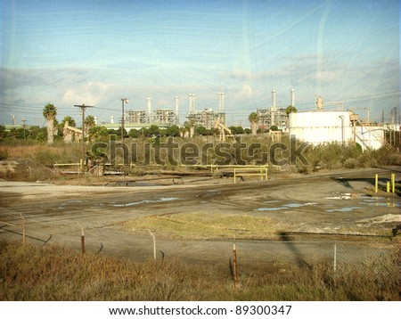 aged and worn vintage photo of oil tanks with industrial factory in background
