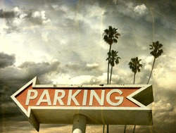 aged and worn vintage photo of parking sign with palm trees