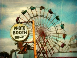 aged and worn vintage photo of photo booth sign with ferris wheel
