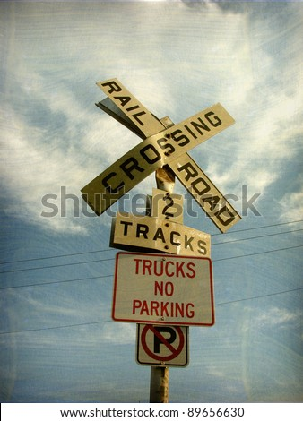 aged and worn vintage photo of railroad crossing sign - stock photo