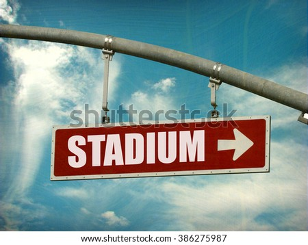 aged and worn vintage photo of stadium sign with arrow