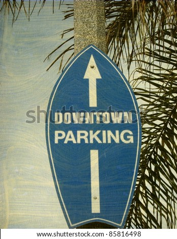 aged and worn vintage photo of surfboard downtown beach city street sign - stock photo