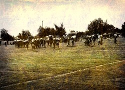 aged and worn vintage photo of unidentifiable young american football players on field