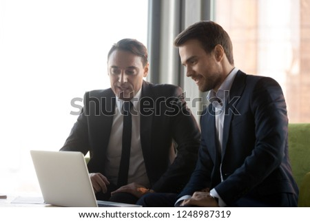 Aged and young businessman at meeting in modern office. Colleagues or client and executive manager sitting on couch looking at laptop screen working together analyzing sales statistics using program #1248987319