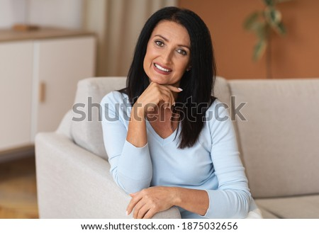 Aged Beauty. Portrait of relaxed mature woman with long dark hair sitting on the couch in living room and posing. Tranquil positive lady looking and smiling at the camera, selective focus Сток-фото ©