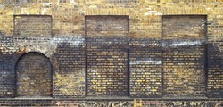 Aged brick wall with four arched bricked up windows with space for text.