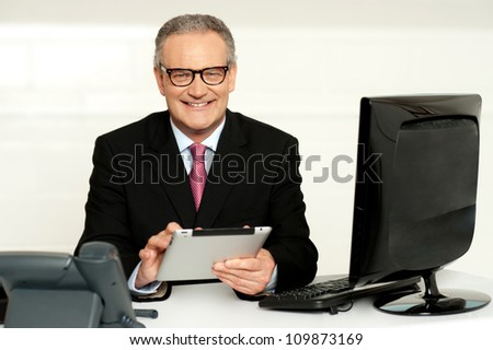 Aged businessman in glasses using tablet sitting in office