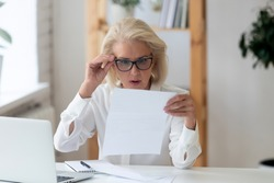 Aged businesswoman sit at workplace desk lowered glasses reads notification feels shocked, bad unexpected news in business letter, financial report, debt notice from bank, bill, taxes increase concept