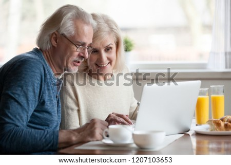 Aged couple busy look at laptop screen while having delicious breakfast at home kitchen, excited senior man and woman use computer during morning routine, elderly wife show something to husband at pc