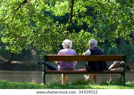 Aged couple enjoy spring morning on the bench near lake in the park