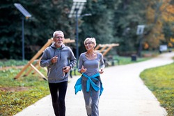 Aged couple jogging in the public park and smile