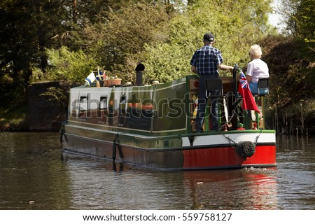 Aged couple on narrow boat in canal, England