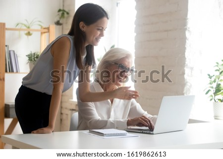 Aged employee sit at workplace desk receives instructions explanations of corporate application from millennial colleague, workmates women discuss task looking at laptop screen, mentoring help concept