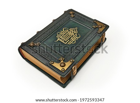 Aged green leather book with gilded calligraphy on the front cover captured isolated.  English translation of the text is: In the name of God, the Most Gracious, the Most Merciful. Stock fotó ©