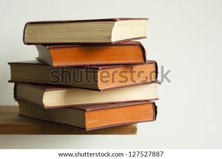 aged hardcover books stack on bookshelf - stock photo