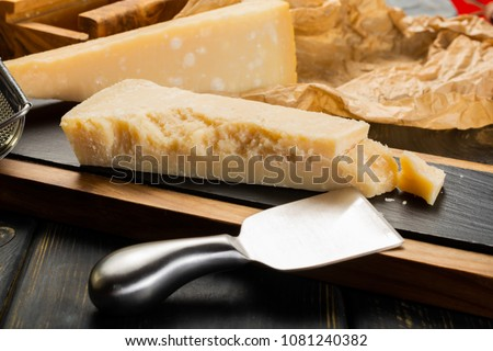 Aged Italian parmesan hard cheese Parmigiano-Reggiano with cheese knife