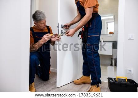 Aged locksmith, repairman, worker in uniform installing, working with house door lock using screwdriver while his colleague bringing him lock plate. Repair, door lock service concept. Horizontal shot