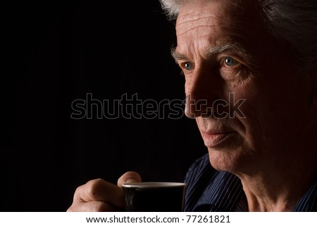 aged man drinking tea on a black - stock photo