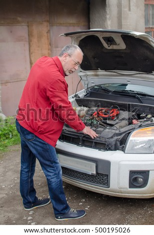 Aged man fixing the car on the street #500195026