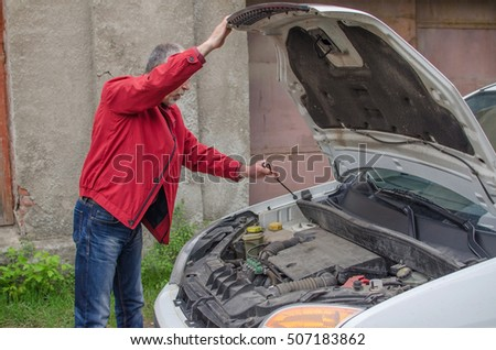 Aged man fixing the car on the street #507183862