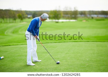 Aged man in blue cardigan, white pants and baseball cap preparing to hit golf ball with club