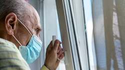 aged man in disposable mask stands at plastic window and holds hand on handle at home in isolation close view