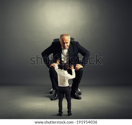 aged man looking at scared man over dark background