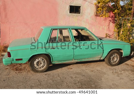 aged old vintage green car in pink wall Cancun Mexico