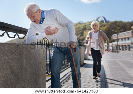 Aged pensioner having pain in his chest on the promenade