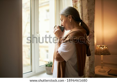 Aged people, lifestyle, retirement and loneliness. Indoor shot of elderly female with gray hair standing by window indoors, spending day at home alone, drinking hot herbal tea, having thoughtful look Foto d'archivio ©