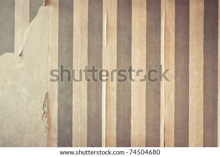 Aged room wall background with torn wallpaper.