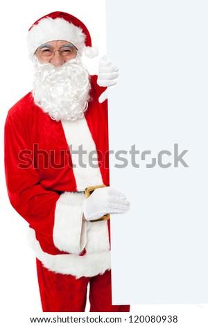 Aged Santa holding blank white banner ad board. Standing beside