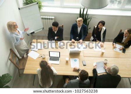 Aged senior businesswoman giving presentation at multiracial group office meeting, female team leader, company boss or business coach presenting corporate plan to executives in boardroom, top view stock photo