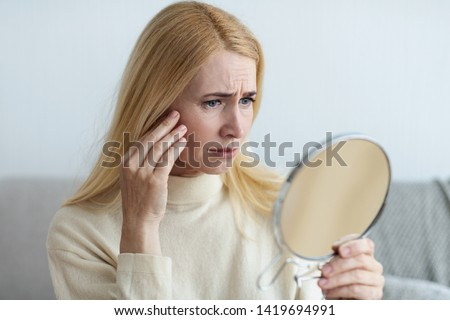 Aged Skin. Mature Sad Woman Looking At Her Wrinkles In Mirror