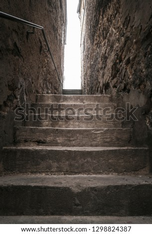 Aged stone stairs, between two old buildings, going up, toward the light, in Luxembourg city. Strong light at the end of the shadowy staircase.