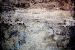 Aged, super-grunge concrete wall in dark, cold color tones. Gloomy, moody feel. Uneven, textured surface. Faded area in the center as copy space.