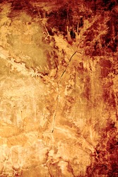 Aged, super-textured background with cracks in golden-rusty (autumn) colors. Faded area for copy space.