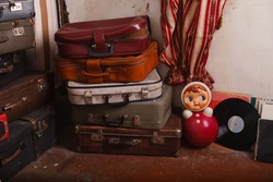 aged things in a traditional Soviet apartment. Retro interior in abandoned house. Outdated furniture and household items. Suitcases and toy roly-poly from 1950s. Not maintained Grandmother's home