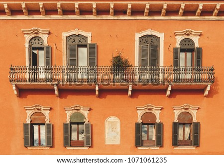 Aged vintage building facade with balcony. Vintage building facade wall. Classic European architecture. Postcard wallpaper. Vintage estate concept. #1071061235