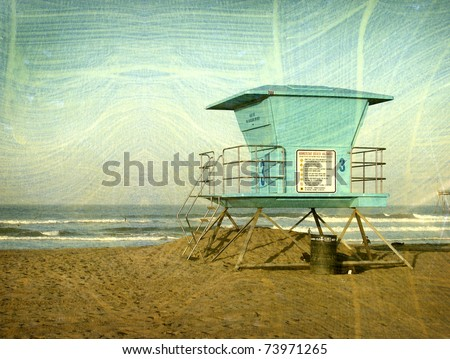 aged vintage photo of lifeguard tower on beach with surfers in background